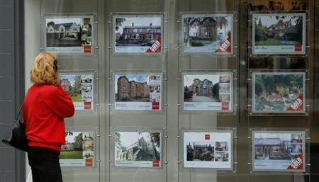 A woman looks at properties advertised for sale in the window of an estate agent in Hale, northern England July 3, 2013. REUTERS/Phil Noble