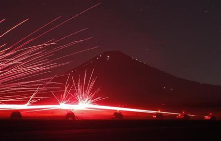 Tracer bullets ricochet off their targets as the Japanese Ground Self-Defence Force Type 74 and Type 90 armoured tanks fire machine guns during a night annual training session at Higashifuji training field in Gotemba, west of Tokyo, August 21, 2012. REUTERS/Issei Kato