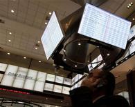 Homem fala ao celular e observa tela eletrônica na bolsa de valores BM&FBovespa em São Paulo. 08/08/2011 REUTERS/Nacho Doce