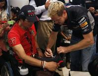 Red Bull Formula One driver Sebastian Vettel of Germany signs his autograph for a fan after speaking at an event at Nissan Motor Co's global headquarters in Yokohama, south of Tokyo October 9, 2013. REUTERS/Yuya Shino