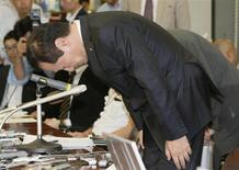 Mizuho Financial Group President Yasuhiro Sato bows during a news conference at the Bank of Japan headquarters in Tokyo, in this photo taken by Kyodo October 8, 2013. REUTERS/Kyodo