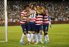 U.S. forward Landon Donovan (10) is mobbed by teammates after scoring against Guatemala on a penalty kick in the second half during their friendly soccer match in San Diego, California July 5, 2013. REUTERS/Mike Blake