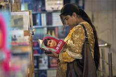 "A woman browses a copy of Malala Yousufzai's book ""I am Malala"" at a book store in Islamabad October 8, 2013. REUTERS/Mian Khursheed"