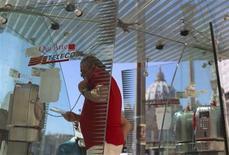 Un hombre usa una cabina telefónica frente a la Basílica de San Pedro en Roma, sep 24 2013. Telecom Italia negó el miércoles que haya comenzado un proceso para vender el 67 por ciento de la empresa brasileña de telefonía móvil Tim Participaçoes. REUTERS/Alessandro Bianchi