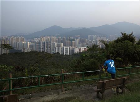 A man stretches his leg at Wilson Trail, a 78 km long-distance footpath at a country park named after former Hong Kong governor David Wilson, as he looks towards Tai Po district at Hong Kong's rural New Territories October 3, 2013. REUTERS/Bobby Yip