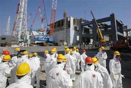 Members of the media wearing protective suits and masks are escorted by TEPCO employees as they go on a visit near the No.4 reactor (C) and its foundation construction (R) for the storage of melted fuel rods at Tokyo Electric Power Co. (TEPCO)'s tsunami-crippled Fukushima Daiichi nuclear power plant in Fukushima prefecture March 6, 2013, ahead of the second-year of anniversary of the disaster. REUTERS/Issei Kato/Files