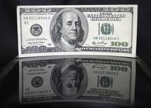 100-долларовая купюра в банке в Токио 2 августа 2011 года. Доллар укрепился к основным валютам в четверг после появления признаков начала диалога между республиканцами и демократами о федеральном бюджете и пределе государственного долга. REUTERS/Yuriko Nakao