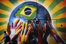 Мужчина смотрит на граффити в Сан-Паулу 10 июля 2013 года. Бразилия повысила процентные ставки в пятый раз подряд в среду и не дала намеков на сворачивание кампании по борьбе с высокой инфляцией, в то время как крупнейшая экономика Латинской Америки пытается набрать скорость. REUTERS/Nacho Doce