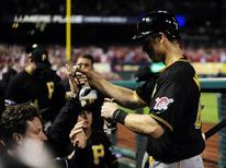 Oct 9, 2013; St. Louis, MO, USA; Pittsburgh Pirates first baseman Justin Morneau (66) celebrates scoring against the St. Louis Cardinals during the seventh inning in game five of the National League divisional series playoff baseball game at Busch Stadium. Jeff Curry-USA TODAY Sports