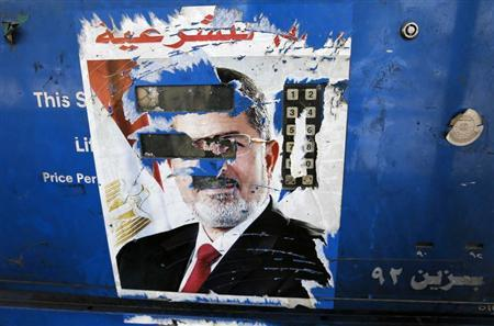The remnants of a poster of ousted Egyptian President Mohamed Mursi are seen at a petrol station in Cairo August 28, 2013. REUTERS/Louafi Larbi