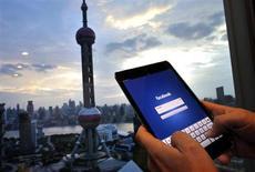 """На фото человек держит iPad с приложением Facebook в офисе в районе финансистов Пудонг в Шанхае 25 сентября 2013 года. Китайский журналист-расследователь, обвинивший в коррупции чиновников, взят под арест, что стало свежим эпизодом в серии попыток властей обуздать критиков с помощью закона о подавлении """"слухов"""" в интернете. REUTERS/Carlos Barria"""