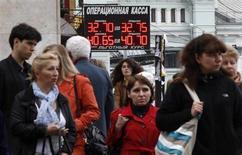 Люди проходят мимо вывески пункта обмена валюты в Москве 31 мая 2012 года. Рубль торговался с незначительной прибылью в четверг, достигнув области, свободной от интервенций Центробанка; на стороне рубля - текущее восстановление нефтяных цен и улучшение ситуации на глобальных рынках, а в целом динамика определяется низкой активностью рынка в ожидании развязки бюджетного кризиса США, а также изменениями пары евро/доллар. REUTERS/Maxim Shemetov