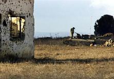 Израильский солдат на танке у полуразрушенной стены дома бывшего сирийского города на Голанских высотах 15 декабря 1999 года. Цены на нефть на короткое время взлетели в четверг после сообщения израильских военных в Twitter, из которого на первый взгляд следовало, что они бомбили аэропорты Сирии. REUTERS