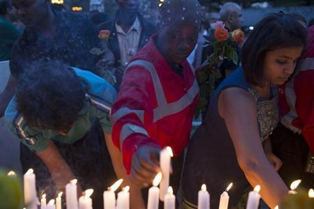 People light candles during a memorial service in front of the Westgate shopping mall in Nairobi, Kenya in honour of the victims of last Saturday's attack by gunmen, September 28, 2013. REUTERS/Siegfried Modola