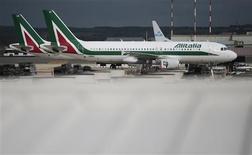 Unos aviones de la aerolínea Alitalia en el aeropuerto internacional Fiumicino en Roma, oct 11 2013. Alitalia, la aerolínea nacional italiana que ha registrado ganancias sólo pocas veces en sus 67 años de historia, se arriesga a colapsar nuevamente mientras el Gobierno intenta encontrar inversores dispuestos a rescatar la firma. REUTERS/Tony Gentile