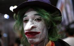 A fan dressed as the Joker from the Batman comic and movie series poses for a photograph at New York's Comic-Con convention October 11, 2013. REUTERS/Mike Segar