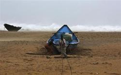 Pescadores amarram seu barco na costa antes de ir para um local mais segura, próximo à vila de Donkuru, no Estado de Andhra Pradesh, sul da Índia. Um forte ciclone avançou sobre a costa leste da Índia neste sábado, matando pelo menos cinco pessoas e forçando cerca de meio milhão a irem para abrigos lotados enquanto a tempestade ameaça deixar uma trilha de devastação em áreas rurais e vilas de pescadores. 12/10/2013. REUTERS/Adnan Abidi