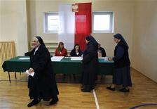 A Catholic nun walks with a ballot paper before casting her vote at a polling station in Warsaw October 13, 2013. REUTERS/Kacper Pempel