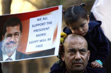 A supporter of ousted Egyptian President Mohamed Mursi, with his young daughter on his shoulders, listens to speeches at a rally in central Sydney August 18, 2013. REUTERS/David Gray