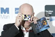 """Man Booker prize shortlist nominee Colm Toibin with his book """"The Testament of Mary"""" takes pictures of photographers during a photocall at the Southbank Centre in London, October 13, 2013. REUTERS/Olivia Harris"""
