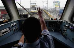 A train operator on Southeast Asia's first light rail transit (LRT) network, which is 29-years-old, signals to a colleague in another train in Manila October 11, 2013. REUTERS/Erik De Castro