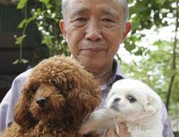 Nguyen Bao Sinh, owner of the Bao Sinh Dog-Cat Resort, poses for a photo with dogs at his resort in Hanoi October 5, 2013. REUTERS/Kham