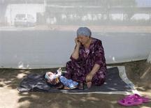 """Узбечка-беженка из Киргизии, сидя рядом внуком двух недель от роду, разговаривает по сотовому телефону в лагере беженцев у киргизо-узбекской границы 23 июня 2010 года. Власти Узбекистана начали внеплановую налоговую проверку в отношении """"дочки"""" Вымпелкома, сообщил российский телекоммуникационный холдинг. Аналитики считают, что это подчёркивает риски для бизнеса в самой населенной стране Центральной Азии. REUTERS/Shamil Zhumatov"""