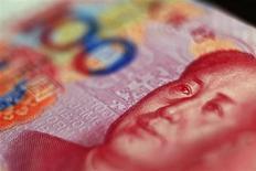 Банкнота в 100 юаней в Пекине 12 мая 2013 года. Китай даст инвесторам, работающим в Лондоне, право купить акции, облигации и инструменты денежного рынка на сумму до 80 миллиардов юаней ($13,1 миллиарда), поощряя попытки британской столицы стать вторым мировым центром торговли в юанях после Гонконга. REUTERS/Petar Kujundzic