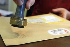 """Работник французской почты ставит печать на письмо в почтовом отделении в Марго 27 ноября 2008 года. Новое приложение для iPhone может возродить привычную пахнущую сургучом рукописную корреспонденцию. С одним высокотехнологичным """"но"""" - писать письма будет робот. REUTERS/Regis Duvignau"""