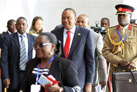 Kenya's President Uhuru Kenyatta (C) is escorted as he arrives for the extraordinary session of the African Union's Assembly of Heads of State and Government on the case of African Relationship with the International Criminal Court (ICC), in Ethiopia's capital Addis Ababa, October 12, 2013. REUTERS/Tiksa Negeri