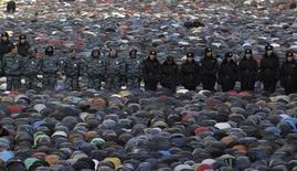 Полицейские стоят среди мусульман, собравшихся на молитву в Москве по поводу исламского праздника Курбан-байрам 15 октября 2013 года. Объединения российских мусульман обратились в МВД с жалобой на взлом их сайтов хакерами, разместившими изображения свиньи с Кораном в зубах, и расценили это как попытку запугивания на фоне роста ксенофобии, вылившейся в погром в столице. REUTERS/Sergei Karpukhin