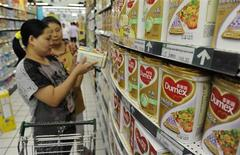 A sales assistant (back) helps a customer to select Dumex milk powder at a supermarket in Hefei, Anhui province August 5, 2013. REUTERS/Stringer