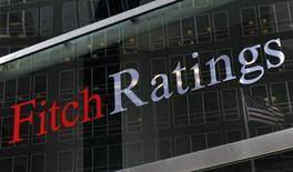 """Флаг США отражается в окне центрального офиса Fitch Ratings в Нью-Йорке 6 февраля 2013 года. Агентство Fitch Ratings предупредило о риске снижения суверенного кредитного рейтинга США """"AAA"""", ссылаясь на политический тупик в Вашингтоне, который препятствует повышению лимита госдолга. REUTERS/Brendan McDermid"""