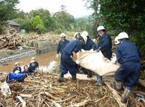 """Спасатели несут тело жертвы оползня, вызванного тайфуном """"Випха"""", на острове Идзуосима 16 октября 2013 года. Восемь человек погибли и более 30 пропали без вести из-за тайфуна """"Випха"""", добравшегося до токийского региона в среду. REUTERS/Kyodo"""