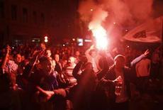 Fãs da seleção de futebol da Bósnia celebram vitória contra a Lituânia em partida classificatória para a Copa do Mundo de 2014, em Sarajevo, 15 de outubro de 2013. Rojões e sinalizadores iluminaram a noite de Sarajevo na terça-feira, quando milhares de moradores saíram às ruas para comemorar madrugada adentro a classificação da Bósnia para a Copa de 2014. 15/10/2013 REUTERS/Dado Ruvic
