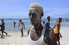 A man, who is covered in sand, poses for a photograph on Lido beach in Mogadishu October 4, 2013.REUTERS/Omar Faruk