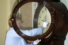 Richard Doerner, a museum specialist for the U.S. Senate, restarts the historic Ohio Clock outside the Senate floor at the U.S. Capitol in Washington, October 17, 2013. REUTERS/Jonathan Ernst