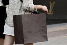 Una mujer con una bolsa de compras de Louis Vuitton a las afueras de una tienda de la firma en París, sep 24 2013. El grupo de artículos de lujo más grande del mundo, LVMH, reportó el martes una desaceleración en las ventas de su división de moda y accesorios de cuero, que incluye las marcas Louis Vuitton, Celine y Dior. REUTERS/Philippe Wojazer