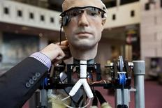 """An engineer makes an adjustment to the robot """"The Incredible Bionic Man"""" at the Smithsonian National Air and Space Museum in Washington October 17, 2013. REUTERS/Joshua Roberts"""