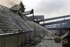 """Bombeiros tentam apagar incêndio em armazén da Copersucar, maior comercializadora de açúcar do mundo, no porto de Santos. O incêndio que atingiu os armazéns da Copersucar na manhã desta sexta-feira foi contido, mas uma """"operação rescaldo"""" de mais dois dias será mantida para evitar que o fogo reacenda, informou a autoridade portuária. 18/10/2013 REUTERS/Paulo Whitaker"""