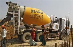 Workers walk in front of an UltraTech concrete mixture truck at the construction site of a commercial complex on the outskirts of the western Indian city of Ahmedabad April 22, 2013. REUTERS/Amit Dave