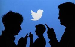 Силуэты людей с телефонами на фоне логотипа Twitter в Варшаве 27 сентября 2013 года. Пенсионер Дональд Хоувэсс завел блог в Twitter примерно год назад по просьбе своей дочери, однако разочаровался, найдя там в основном знаменитостей, а не своих друзей. REUTERS/Kacper Pempel