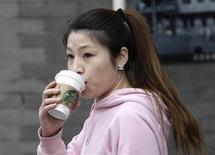 Женщина пьет кофе из кафе Starbucks в Пекине 19 апреля 2012 года. Starbucks Corp устанавливает для потребителей в Китае цены выше, чем на других рынках, чтобы получить таким способом большую прибыль, говорится в репортаже официального Центрального телевидения Китая (CCTV).REUTERS/Jason Lee