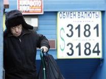 Мужчина проходит мимо вывески пункта обмена валюты в Москве 13 января 2009 года. Рубль торговался недалеко от одномесячных максимумов в понедельник в надежде на сохранение повышенной денежной эмиссии ФРС для стимулирования экономики США, пострадавшей от бюджетного кризиса, а также перед крупными налогами ближайшей недели. REUTERS/Sergei Karpukhin
