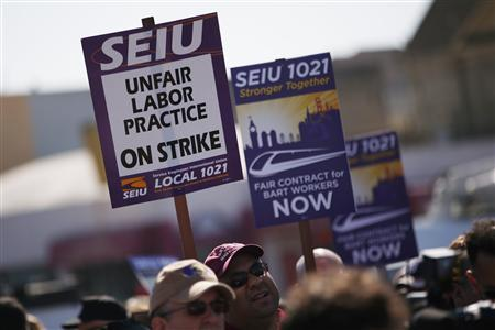 Demonstrators hold signs in support of striking Bay Area Rapid Transit (BART) workers outside Lake Merritt Station in Oakland, California October 18, 2013. REUTERS/Stephen Lam