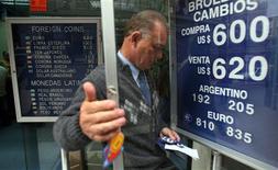 Un operador en una casa de intercambio de divisas en el centro de Santiago, oct 13 2008. Las monedas latinoamericanas iniciarían la semana alentadas por el aumento del apetito global por el riesgo ante una baja de las tasas de los bonos del Tesoro de Estados Unidos, pero estarán a la expectativa de un reporte oficial del empleo estadounidense para ver si consolidan la tendencia por lo que resta del año. REUTERS/Ivan Alvarado