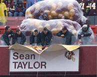 Workers unveil a banner of Washington Redskins slain player Sean Taylor as Taylor is inducted into the Redskins Ring of Honor prior to their NFL football game against the New York Giants in Landover, Maryland, November 30, 2008.