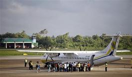 People form a line to board a plane in Yangon airport October 2, 2013. REUTERS/Soe Zeya Tun