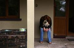Ann Cronin sits with a dog as she packs her belongings in preparation for her family's emigration from her hometown of Ennis in County Clare, to New Zealand September 27, 2013. REUTERS/Cathal McNaughton