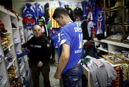 A tourist tries on a Bosnian national soccer team jersey at a shop in the old part of the city, Bascarsija, in Sarajevo, October 16, 2013. REUTERS/Dado Ruvic